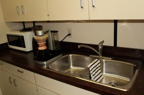 Kitchen with fridge, microwave, dishes, coffee maker, and sink.